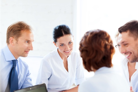 smiling businesswoman with team on meeting in office photo