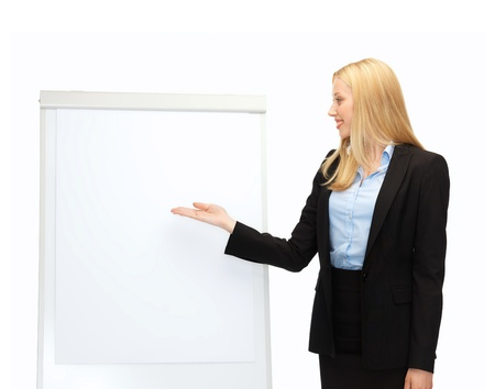 smiling businesswoman pointing at white blank flipchart photo