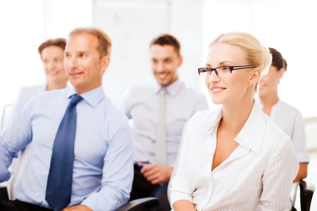 business concept - smiling businessmen and businesswomen on conference photo