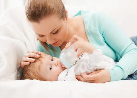 gl�ckliche Mutter und entz�ckendes Baby mit Milchflasche Lizenzfreie Bilder