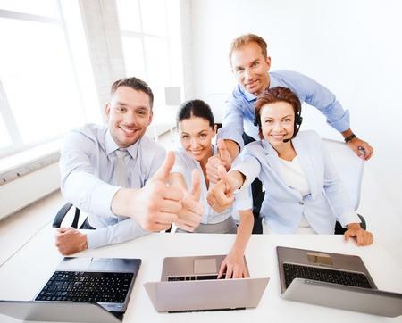 事業コンセプト - コール センターで親指を現してオフィス労働者のグループ