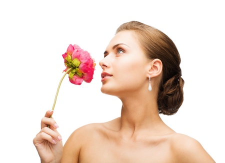 beauty and jewelry - woman wearing earrings and smelling flower photo