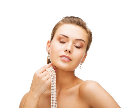 pearl necklace: beauty and jewelery concept - beautiful woman with pearl earrings and necklace Stock Photo