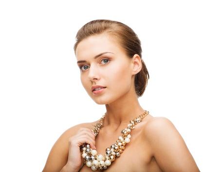 jewellery: beauty and jewelery concept - beautiful woman wearing statement necklace with pearls