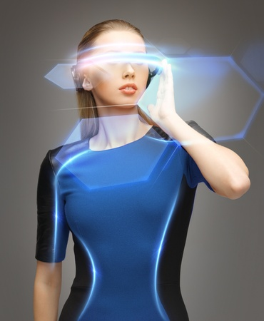VIRTUAL REALITY: beautiful woman in futuristic glasses and blue dress