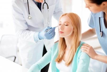 helder beeld van de mannelijke plastisch chirurg met de patiënt