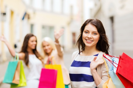 holiday spending: shopping and tourism concept - beautiful girls with shopping bags in ctiy