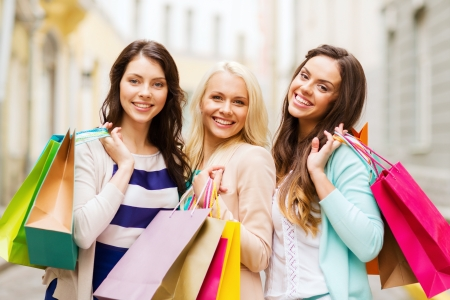 shopping bag: shopping and tourism concept - beautiful girls with shopping bags in ctiy