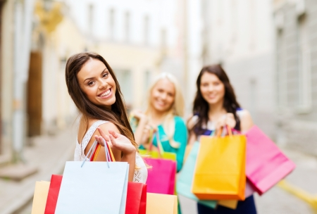 overspending: shopping and tourism concept - beautiful girls with shopping bags in ctiy