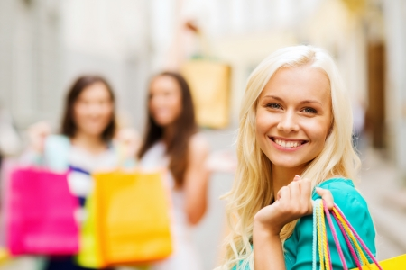 shopping and tourism concept - beautiful girls with shopping bags in ctiy photo