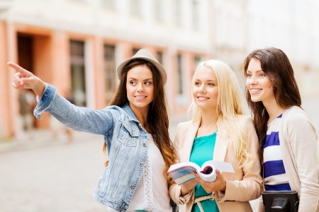 sightseeing tour: holidays and tourism concept - beautiful girls looking for direction in the city Stock Photo