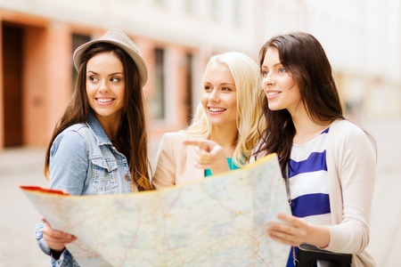 urban travel: holidays and tourism concept - beautiful girls looking for direction in the city Stock Photo