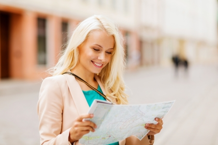 lost city: holidays and tourism concept - beautiful girl looking into tourist map in the city Stock Photo