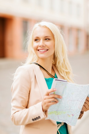 holidays and tourism concept - beautiful girl looking into tourist map in the city photo