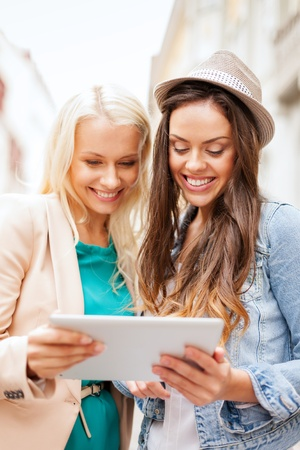 holidays and tourism concept - beautiful girls toursits looking into tablet pc in the city photo