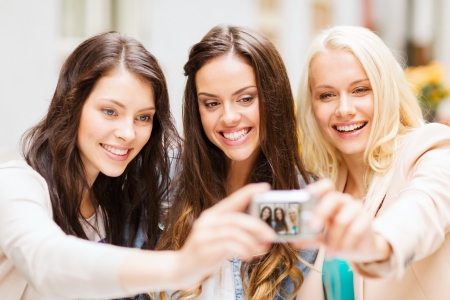 holidays and tourism concept - beautiful girls taking picture in cafe in city photo