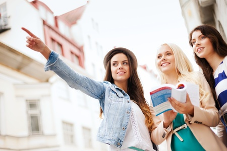 travel guide: holidays and tourism concept - beautiful girls looking for direction in the city Stock Photo