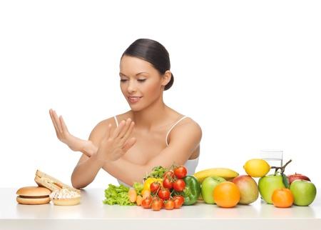 ハンバーガーを拒絶する果物を持つ女性の写真 写真素材