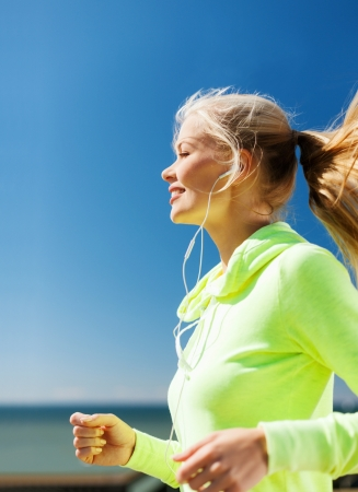 outdoor sports: sport and lifestyle concept - woman doing running outdoors