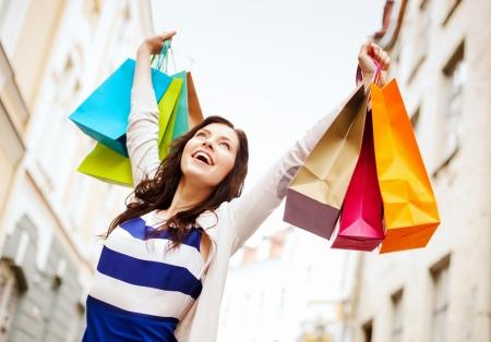 ショッピングや観光のコンセプト - 市のレジ袋と美しい女性