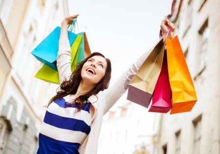 shopping and tourism concept - beautiful woman with shopping bags in ctiy 版權商用圖片