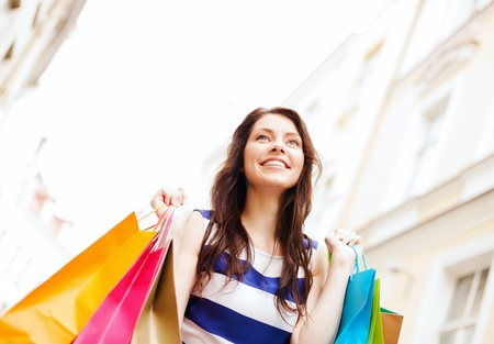 holiday spending: shopping and tourism concept - beautiful woman with shopping bags in ctiy Stock Photo