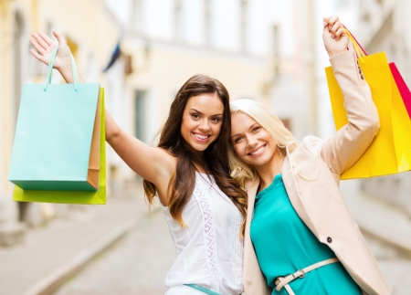 girlfriend: shopping and tourism concept - beautiful girls with shopping bags in ctiy