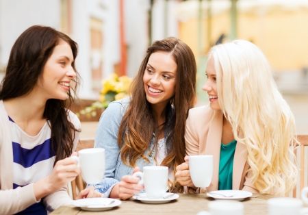 friends drinking: holidays and tourism concept - beautiful girls drinking coffee in cafe Stock Photo