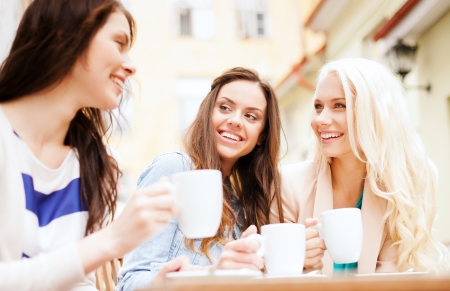 holidays and tourism concept - beautiful girls drinking coffee in cafe photo