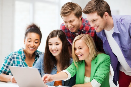 education concept - smiling students looking at laptop at school