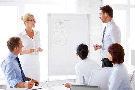équipe de sourire d'affaires travaillant avec tableau de conférence dans le bureau