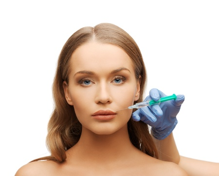cosmetic surgery concept - woman face and beautician hand with syringe photo