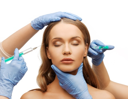 cosmetic surgery concept - woman face and beautician hands with syringes photo