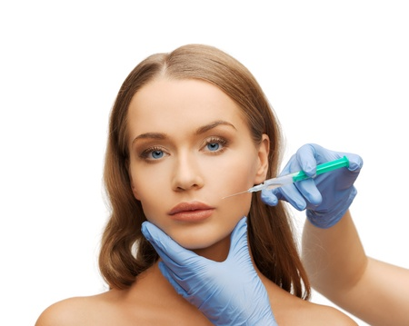 cosmetic surgery concept - woman face and beautician hands with syringe photo
