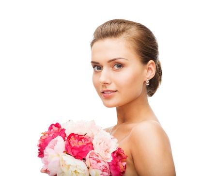 beauty and jewelry - woman wearing earrings and holding flowers photo
