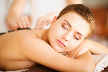 beauty concept - woman in spa salon with hot stones photo