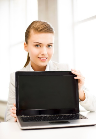 picture of smiling businesswoman with laptop in office photo