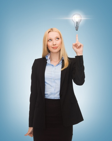 brilliant ideas: business, energy and environment concept - woman pointing at light bulb