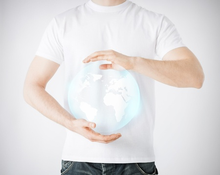 news, technology and environment concept - man hands holding sphere globe photo