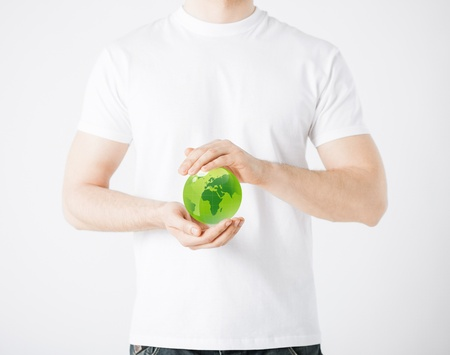 alternative energy source: environment and technology concept - man hands holding green sphere globe Stock Photo