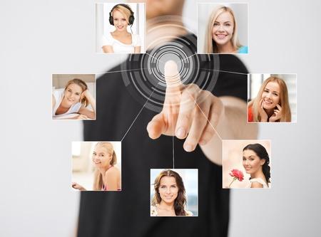 iconos contacto: la tecnolog�a y la comunicaci�n - el hombre presionando el bot�n en la pantalla virtual con iconos de contacto Foto de archivo