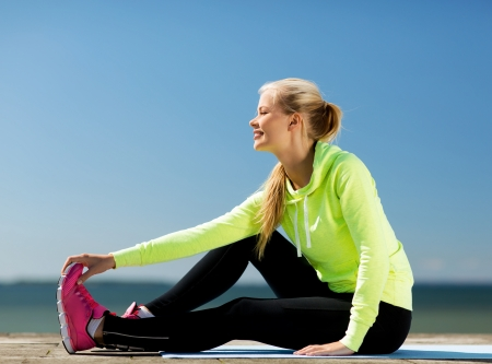 warm up: sport and lifestyle concept - woman doing sports outdoors Stock Photo