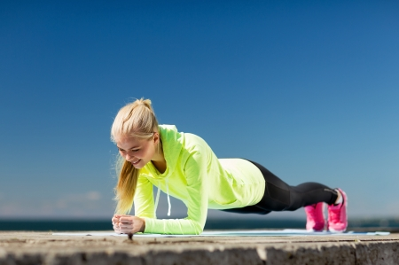 abs: sport and lifestyle concept - woman doing sports outdoors Stock Photo