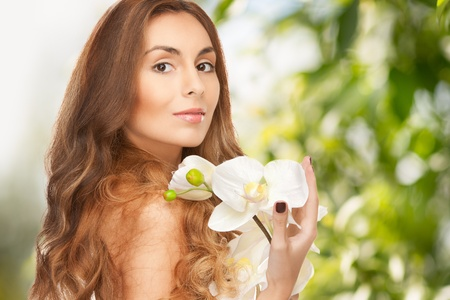 beauty and eco cosmetology concept - beautiful woman with orchid flower photo