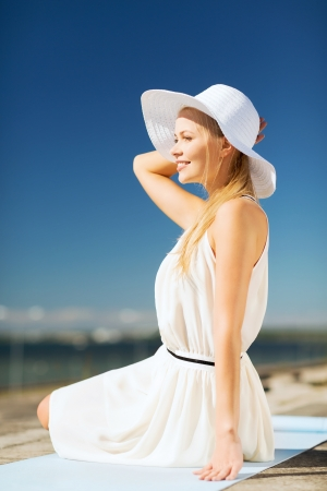 fashion and lifestyle concept - beautiful woman in hat enjoying summer outdoors