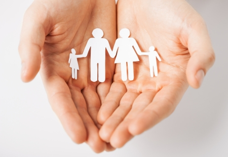 charitable: man hands showing family of paper men