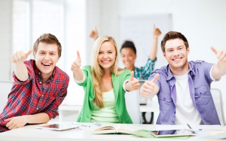 admission: education concept - happy team of students showing thumbs up at school Stock Photo