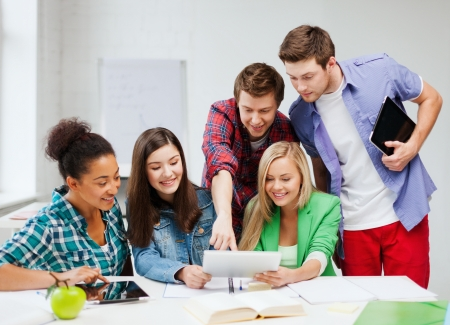 university application: education concept - smiling students looking at tablet pc at school Stock Photo