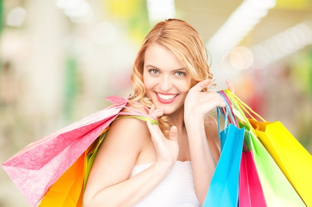 attractive woman holding color shopping bags in mall Stock Photo - 20772039