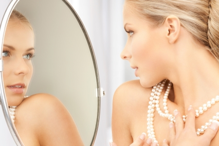 pearl: woman with pearl necklace looking in the mirror